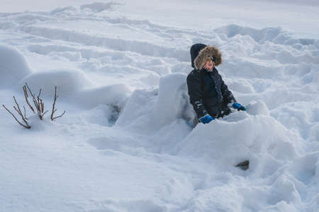 Little boy sitting in a deep snow after heavy snowfall, Tromso, Norway