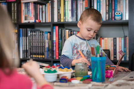 Little caucasian boy sitting at a table at home and having fun with kids paint Stock Photo