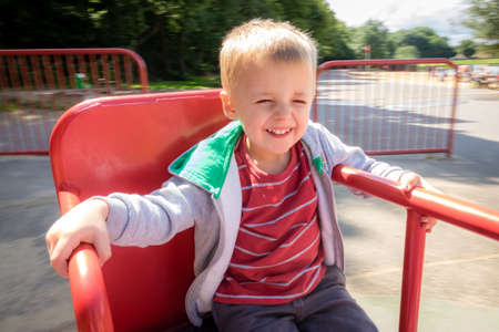 Little cute Caucasian boy spinning round seating on a carousel metal chair in an playground in summer Imagens