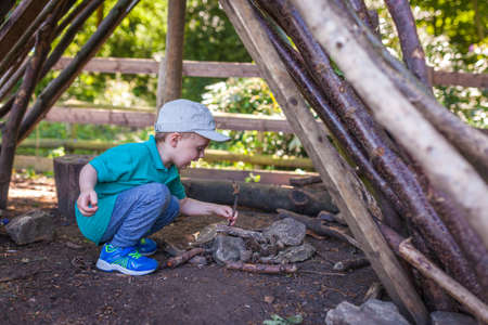 Little boy building a campfire while on a trip into the woods Standard-Bild - 122339486