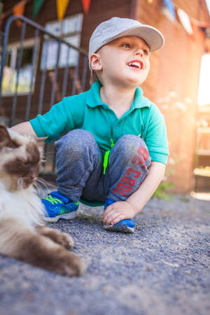 Portrait of a happy little boy stroking cat fur on the farm