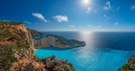Panoramic view of the sun shining over cliffs in Shipwreck Cove in summer on Zante Island, Greece Stock Photo