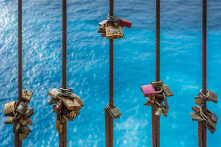 Zakynthos, Greece -  April 2019 : Colorful riusted padlocks locked to the railing on a fence on a viewpoint above Shipwreck Cove Navagio Beach, Zakynthos Island Editorial