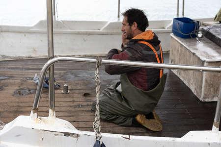 Zakynthos, Greece -  April 2019 : Fisherman talking on a mobile phone on his boat in Zakynthos Port Zakynthos City Editorial