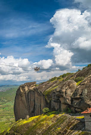 Ropeway transport of a basket cubicle with person and good to the top of a rock where Holy Monastery of Great Meteoron is located, Meteora, Greece