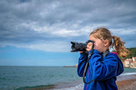 Cute little caucasian girl taking photographs on the seaside in Montenegro