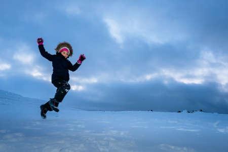 Bambina felice che salta nella neve tra i meravigliosi paesaggi invernali in Norvegia