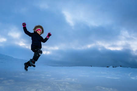 Happy little girl jumping in the snow among the wonderful winter scenery in Norway 版權商用圖片