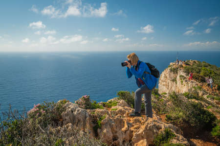 Zakynthos, Greece -  April 2019 : Female tourist standing on the edge of a cliff and photographing the stunning cliffs in Shipwreck Cove in summer