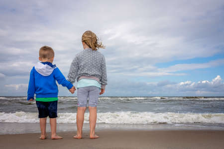 Little boy and girl standing on the sand waiting for wave to come on the beach in summer