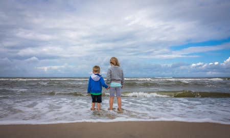 Little boy and girl standing in the sea waters on the beach in summer
