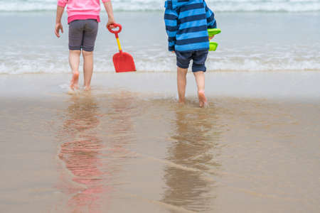 Little boy and girl playing with colorful plastic toy shovels in the water on the beach in summer Stockfoto