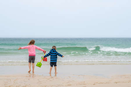 Little boy and girl carrying colorful plastic toy shovels running towards the water on the beach in summer