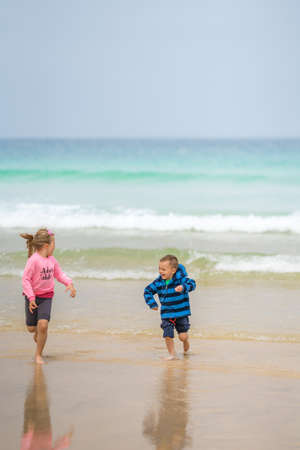 Little boy and girl running away from the incoming waves on the beach in summer