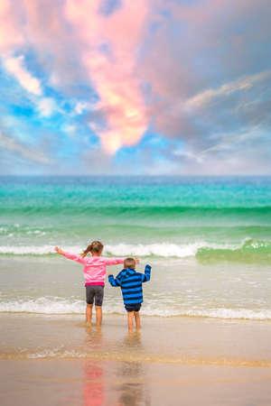 Kleine jongen en meisje staan op het strand aan de kust en wachten op de inkomende golven in de zomer
