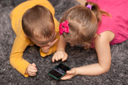 Little children watching cartoon on a smartphone while lying on the carpet in a room at home 写真素材 - 126594486