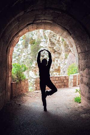 Silhouette einer Frau, die im Sommer Yoga in einem dunklen Tunnel praktiziert