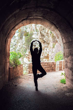 Silhouette of a woman practicing yoga in a dark tunnel in summer