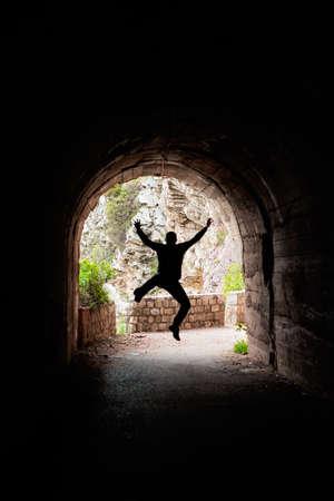 Silhouette eines Mannes, der in einem dunklen Tunnel auf dem Wanderweg in der Bucht von Petrovac, Montenegro, springt Standard-Bild