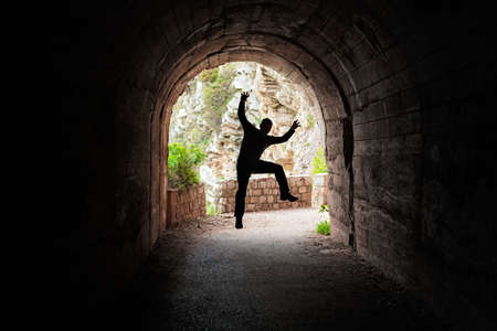 Silhouette of a man jumping in a dark tunnel on the walking path in Petrovac bay,Montenegro Фото со стока