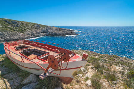 Old wooden abandoned fisherman boat on the shore in Porto Limnionas, Zakynthos Zante Island, Greece Reklamní fotografie - 129952181