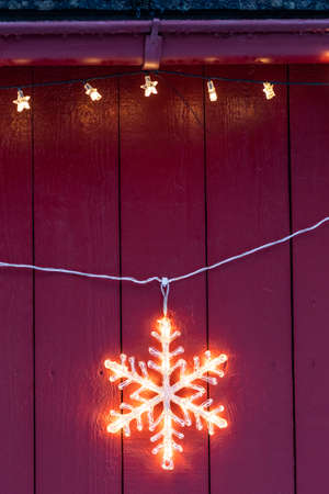 Electric star hanging outside wooden home during Christmas in winter
