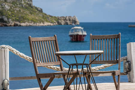 Wooden chairs by the empty outdoor restaurant table on a deck platform in Agios Nikolaos beach on Zakynthos Island, Greece Banque d'images