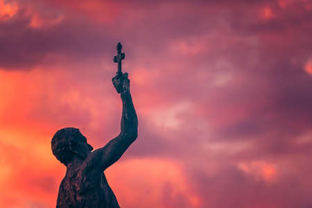 Catcher of a Cross statue in Ohrid town during dramatic sunset, Northern Macedonia Stock Photo