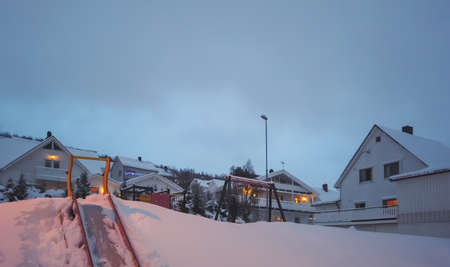 Children playground covered in a layer of deep snow, Tromso in Norway 免版税图像