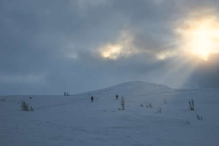 Unidentifiable people walking towards Storsteinen mountain summit and peak in the snow among the wonderful winter scenery, Norway
