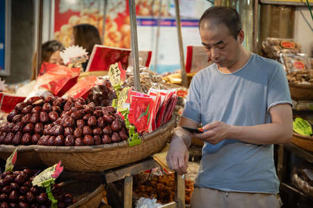 Xian, China -  July 2019 : Bored fruit seller checking his smartphone on a stall in Muslim Quarter Редакционное