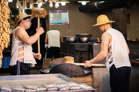 Xian, China -  July 2019 : Two men hitting hard with big wooden hammers to crack grain which will be used in making of sweet snack for sale on the street, Muslim Quarter
