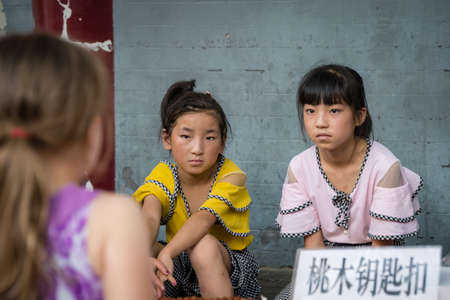 Xian, China -  July 2019 : Two little Chinese girls looking at a Caucasian girl standing in front of a souvenir stand on the street in the Muslim Quarter