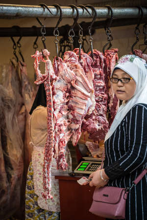 Xian, China -  July 2019 : Muslim woman buying lamb and cow carcass meat from the street food vendors shop in the Muslim quarter of Xian town, Shaanxi Province Редакционное