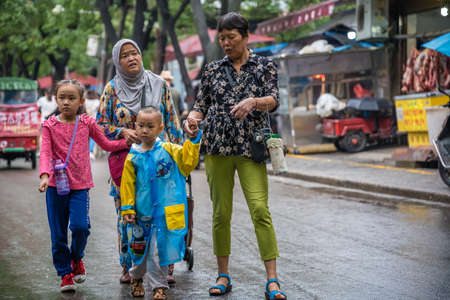 Xian, China -  July 2019 : Muslim family shopping and walking in rain on the road in the Muslim Quarter
