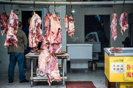Xian, China -  July 2019 : Lamb and cow carcasses hanging on hooks in the Muslim quarter of Xian town, Shaanxi Province