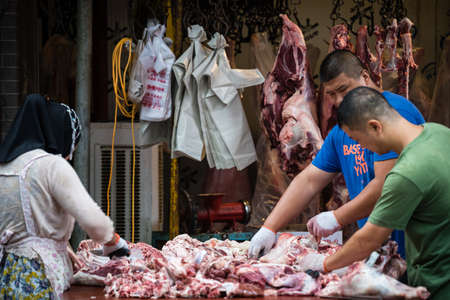 Xian, China -  July 2019 : Two men workers cutting and segregating lamb and cow carcass meat and bones, the street food vendors in the Muslim quarter of Xian town, Shaanxi Province