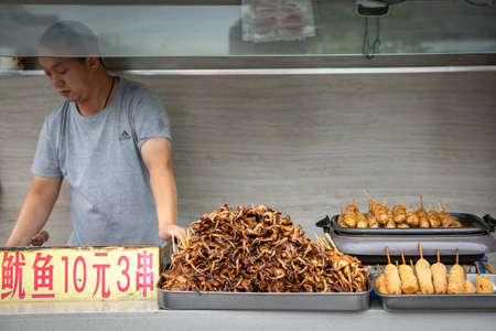 Xian, China -  July 2019 : Meat, snacks, calamari and fried baby octopus vendor selling food on the street in the Muslim Quarter Banco de Imagens - 133522110