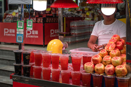 Xian, China -  July 2019 : Man selling plastic cup filled with freshly squeezed pomegranate juice in a stall in Muslim Quarter in Xian town, Shaanxi Province