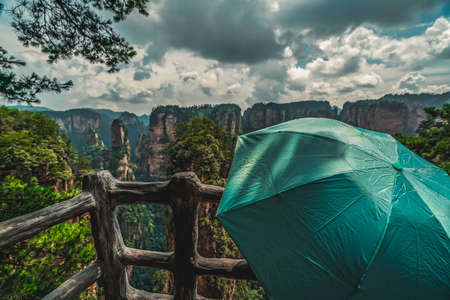 Tourist holding green umbrella admiring the view and  on the scenic viewpoint, Avatar mountains nature park, Zhangjiajie, China