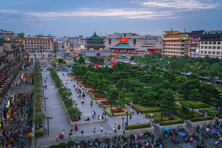 Xian, China -  July 2019 : Crowds walking on streets and town square with landmark Drum Tower in the background, Shaaxi Province