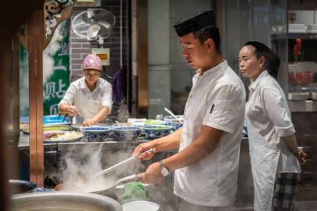 Xian, China -  August 2019 : Chinese chef preparing hot food on a food stall operating at night on the street in the Muslim Quarter Редакционное