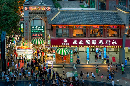 Xian, China -  July 2019 : Crowds walking among shops in the bustling streets of the Muslim Quarter in the evening as seen from the viewpoint in rum Tower, Xian city, Shaaxi Province
