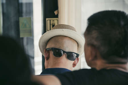 Xian, China -  July 2019 : A chinese man wearing his sunglasses on the back of his shaved head with a hat that gives the illusion of a face, public transport Editorial