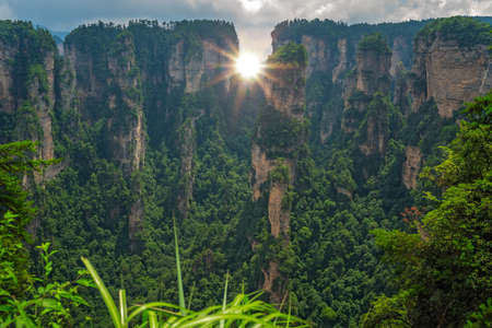 Sun shining through the vertical karst pillar rock formations as seen from the Enchanting terrace viewpoint, Avatar mountains nature park, Zhangjiajie, China 版權商用圖片