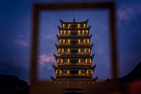 Photographed at dusk traditional chinese style wooden tower pagoda seen through the frame,  Wulingyuan entrance to the Zhangjiajie national park, Hunan Province, China