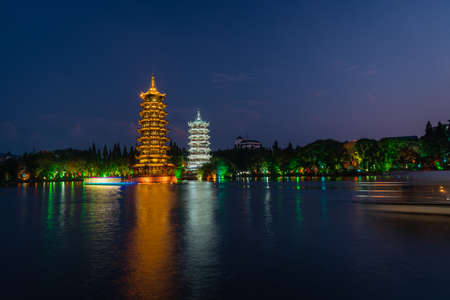 Tourist boats sailing in front of illuminated at night Sun and Moon Pagodas Towers at Shanhu or Shan Lake in Guilin town, Guangxi Province, China