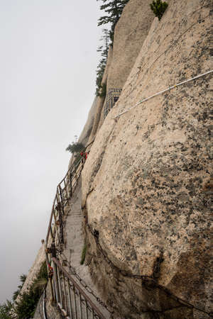 Stone steps cut on a side of a mountain rock leading to the dangerous and perilous Plank Walk trail, closed for public access due to bad weather conditions, Huashan mountain, Xian, Shaanxi Province, China Stock fotó