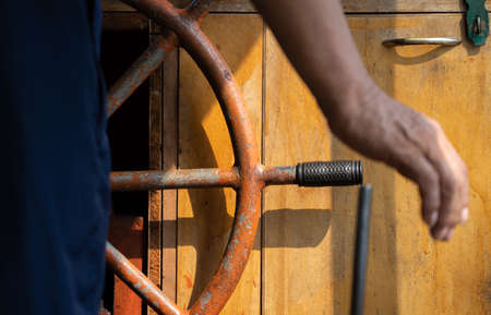 Wooden boat captain standing in front of the steering wheel of an old ship, China