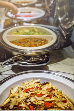Fried noodles and boiled pakchoy in a serving bowl as a asian style breakfast buffet on the table in hotel cafeteria, China